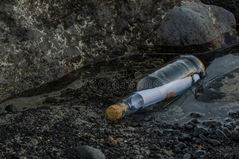Сообщение в бутылке на пляже с черным утесом лавы стоковое изображение