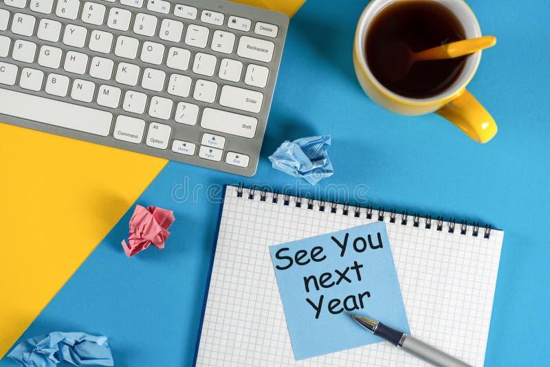 Сообщение дела видит вас в следующем году написанные на тетради, с клавиатурой, канцелярские товары на голубой таблице в предпосы стоковые фото