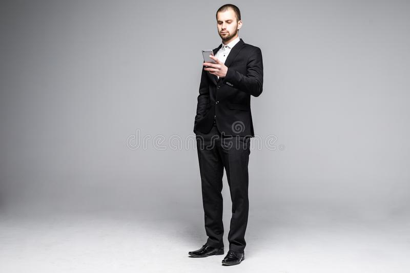 Сообщение молодого бизнесмена печатая на экране касания smartphone Полный портрет длины тела изолированный над белой предпосылкой стоковые фотографии rf