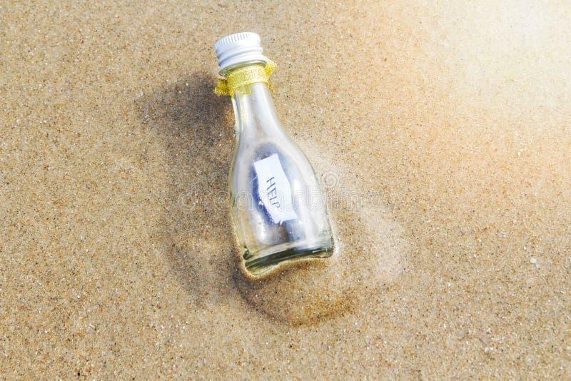 Сообщение ` ПОМОЩИ ` в стеклянной бутылке стоковое фото rf