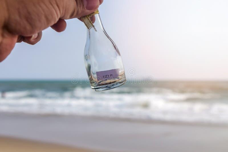 Сообщение ` ПОМОЩИ ` в стеклянной бутылке стоковые фотографии rf