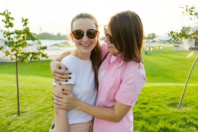 Сообщение родителя и подростка, матери обнимая дочь Зона лужайки, воссоздания и развлечений предпосылки зеленая стоковая фотография