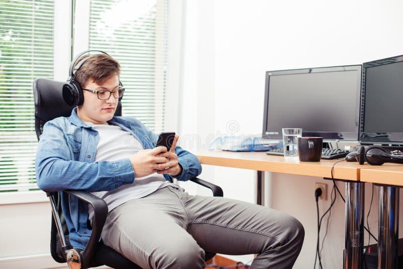 Сообщение чтения молодого человека с smartphone стоковое изображение