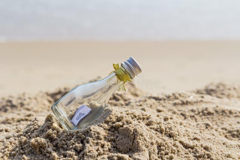 Сообщение SOS в бутылке на пляже стоковая фотография