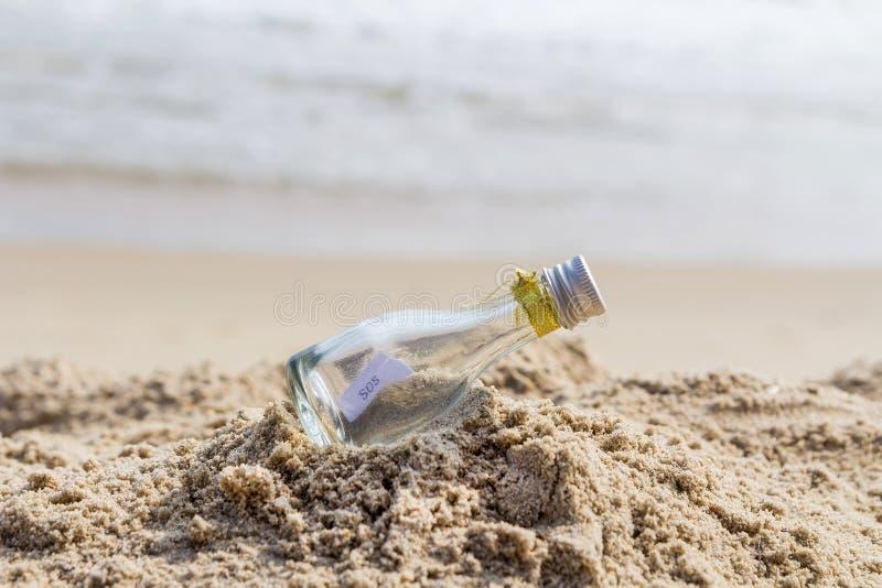 Сообщение SOS в стеклянной бутылке стоковое фото