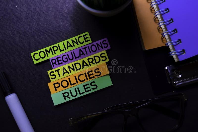 Соответствие, регулировки, Strandards, политики, правила отправляет SMS на липких примечаниях изолированных на черном столе Конце стоковые фотографии rf