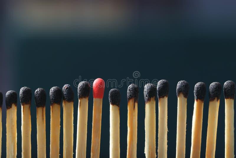 Соответствуйте положению вне от других на темной предпосылке стоковое изображение