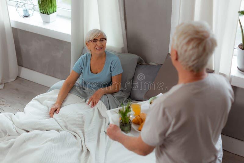 Соперничанная дама получая завтрак для того чтобы положить в постель от ее супруга стоковое изображение