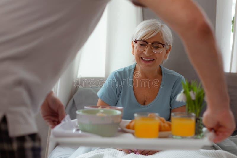 Соперничанная дама смотря завтрак пока лежащ в кровати стоковая фотография