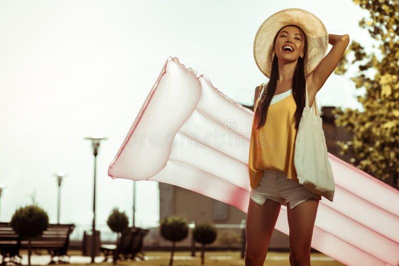 Соперничанная женщина идя к пляжу с тюфяком для плавать стоковые изображения