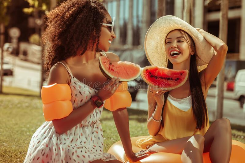 Соперничанные девушки говоря и держа части арбуза в руках стоковая фотография