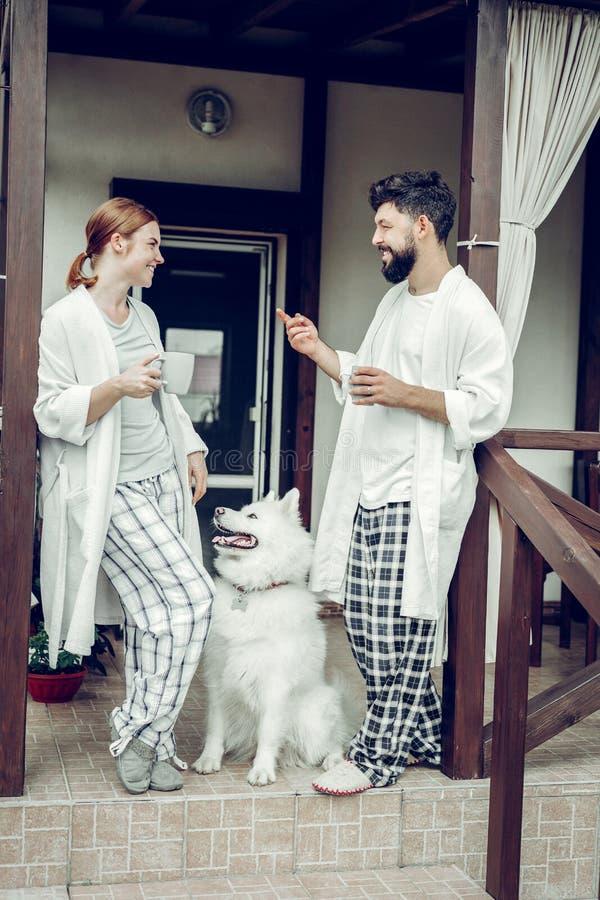 Соперничанные пары наслаждаясь кофе утра пока samoyed сидя рядом с стоковые фото