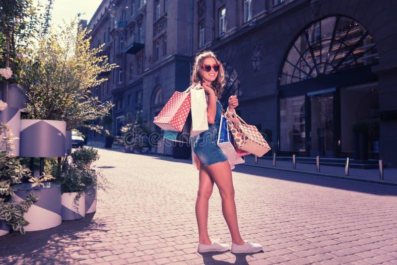 Соперничанный shopaholic стоящий близко причудливый бутик с хозяйственными сумками стоковое фото rf