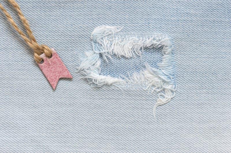 Сорванная предпосылка джинсовой ткани с биркой Текстура ткани голубых джинсов стоковая фотография