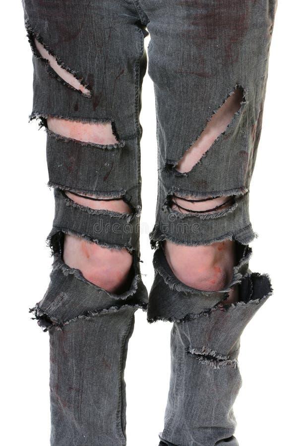 Сорванные и кровопролитные джинсы стоковая фотография