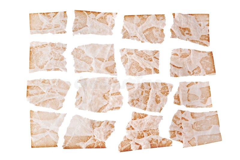 Сорванные листы коричневой достигшей возраста бумаги на белом конце предпосылки вверх, неровные клоки старого бумажного дизайна,  стоковые изображения