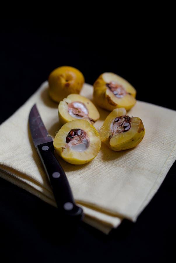 Сорванный желтый цвет отрезал половинные плодоовощи Chaenomeles айвы на кудели чая стоковые фотографии rf