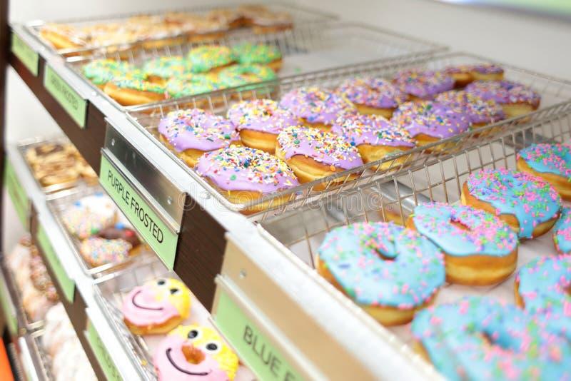Сортировал свежие donuts на стеллажах для выставки товаров стоковое изображение