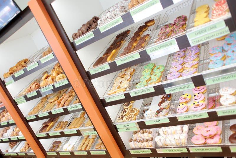 Сортировал свежие donuts на стеллажах для выставки товаров стоковое фото rf
