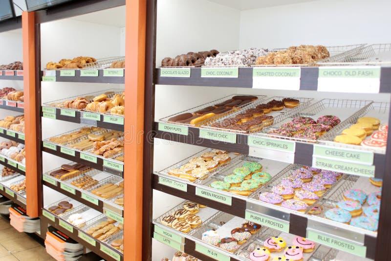 Сортировал свежие donuts на стеллажах для выставки товаров стоковые изображения
