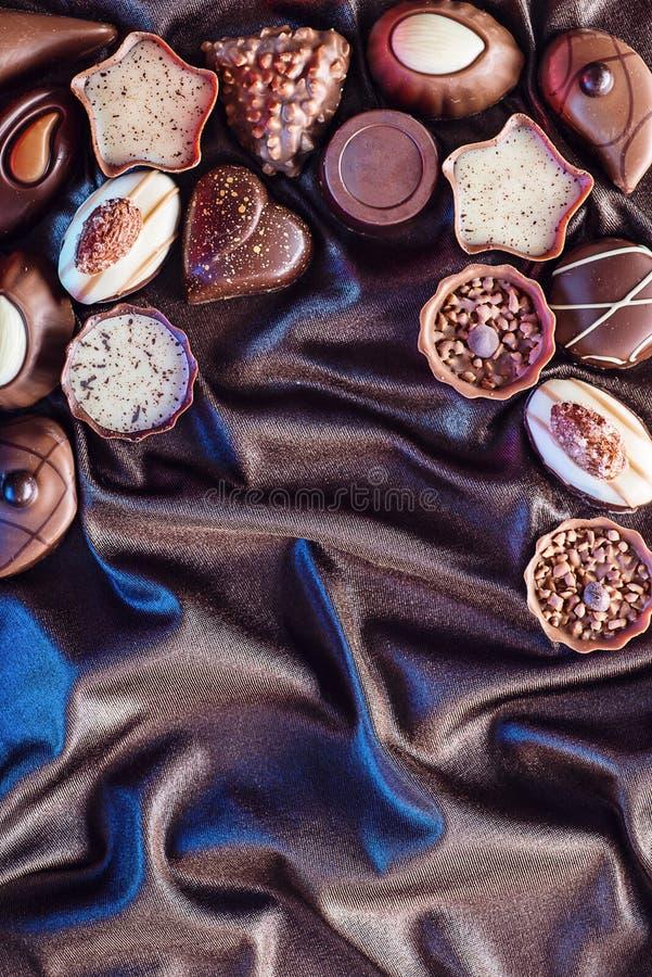 Сортированная очень вкусная предпосылка пралине шоколада на предпосылке сатинировки и голубых светах, месте для текста, фотографи стоковая фотография rf