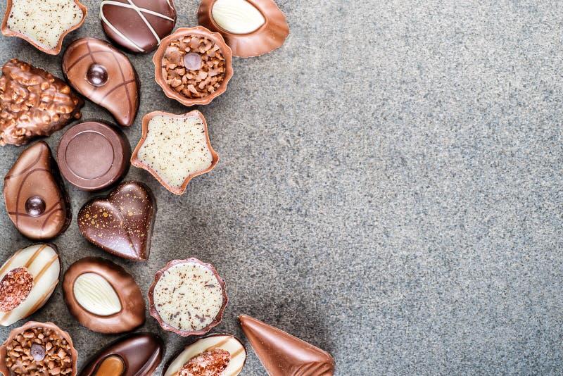 Сортированная очень вкусная предпосылка пралине шоколада на серой текстуре, месте для текста, фотографии продукта для patisserie стоковое фото rf