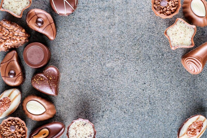 Сортированная очень вкусная предпосылка пралине шоколада на серой текстуре, месте для текста, фотографии продукта для patisserie стоковые фотографии rf