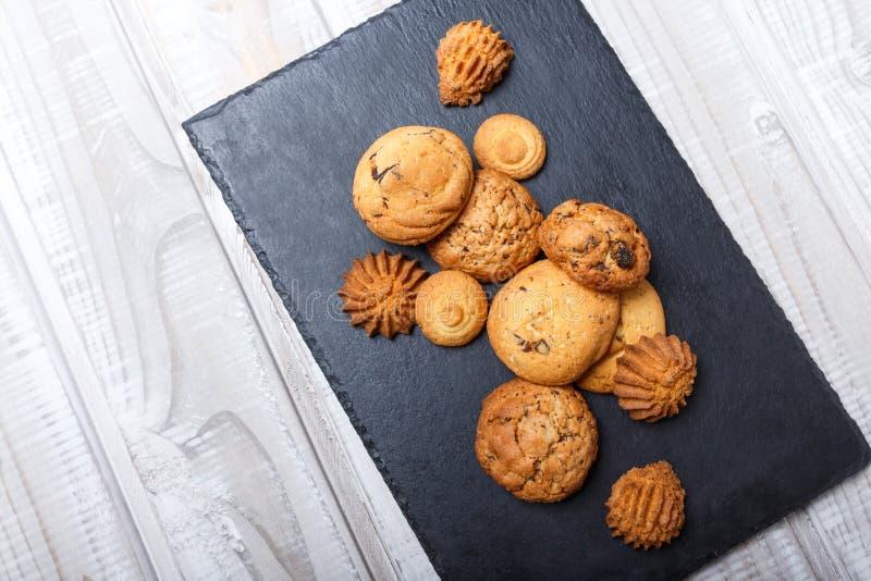 Сортированные печенья с обломоком шоколада, изюминкой овсяной каши на каменной предпосылке шифера на деревянном конце предпосылки стоковое фото