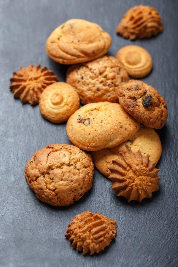 Сортированные печенья с обломоком шоколада, изюминкой овсяной каши на каменной предпосылке шифера на деревянном конце предпосылки стоковая фотография