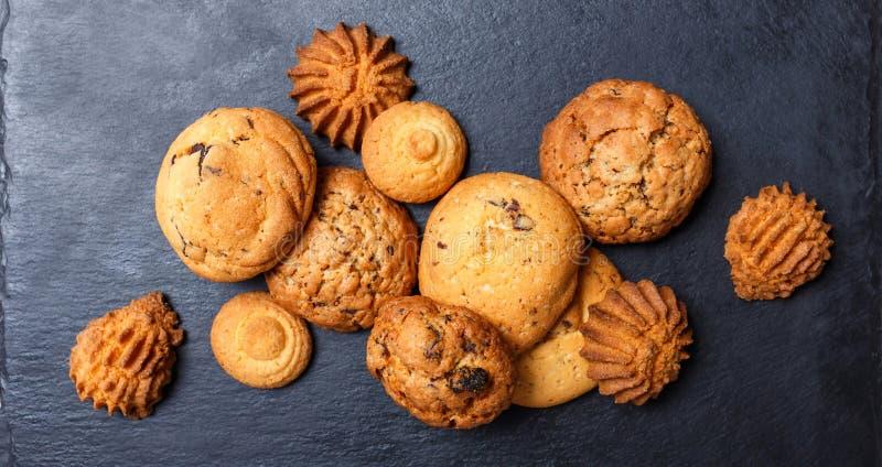 Сортированные печенья с обломоком шоколада, изюминкой овсяной каши на каменной предпосылке шифера на деревянном конце предпосылки стоковое фото rf
