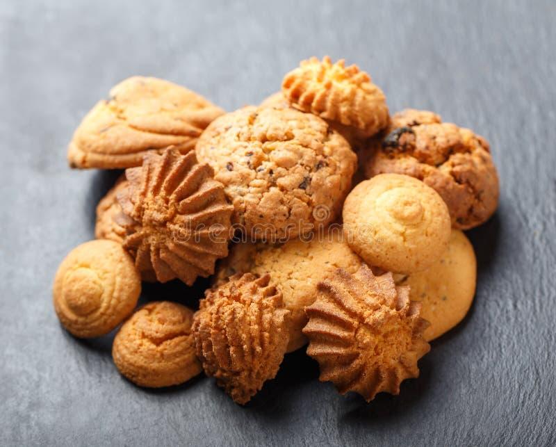 Сортированные печенья с обломоком шоколада, изюминкой овсяной каши на каменной предпосылке шифера на деревянном конце предпосылки стоковое изображение
