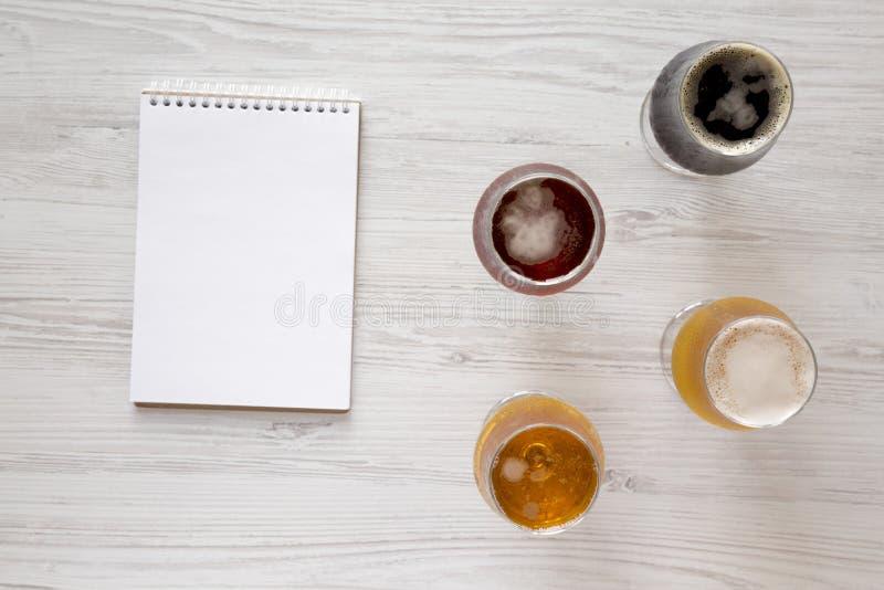 Сортированные пив на белой деревянной предпосылке, взгляде сверху r   стоковые фото