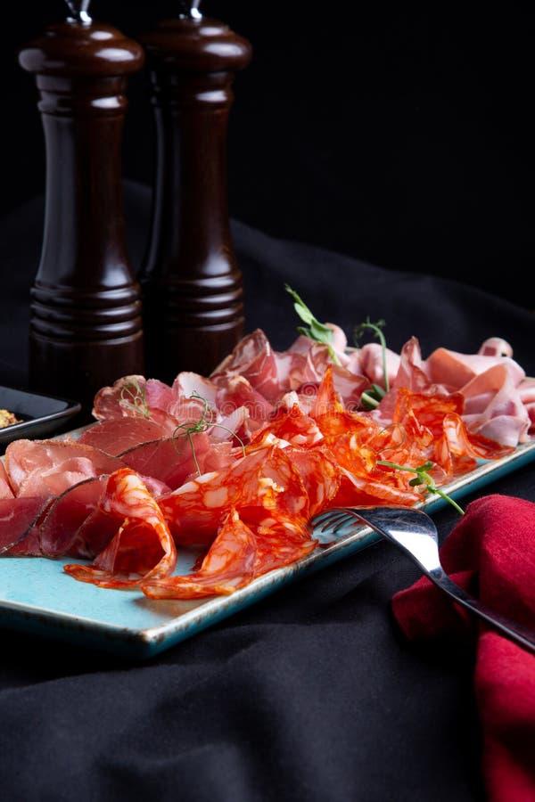 Сортированные холодное мясо, ветчина, куски ветчина, отрывистое говядины, салями, мясо и мустард на черной предпосылке Закуска мя стоковая фотография rf