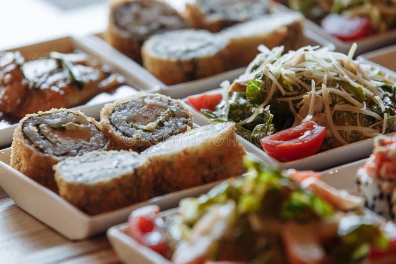 Сортированные японские блюда в белых квадратных плитах на деревянных стойках на предпосылке таблицы стоковое изображение