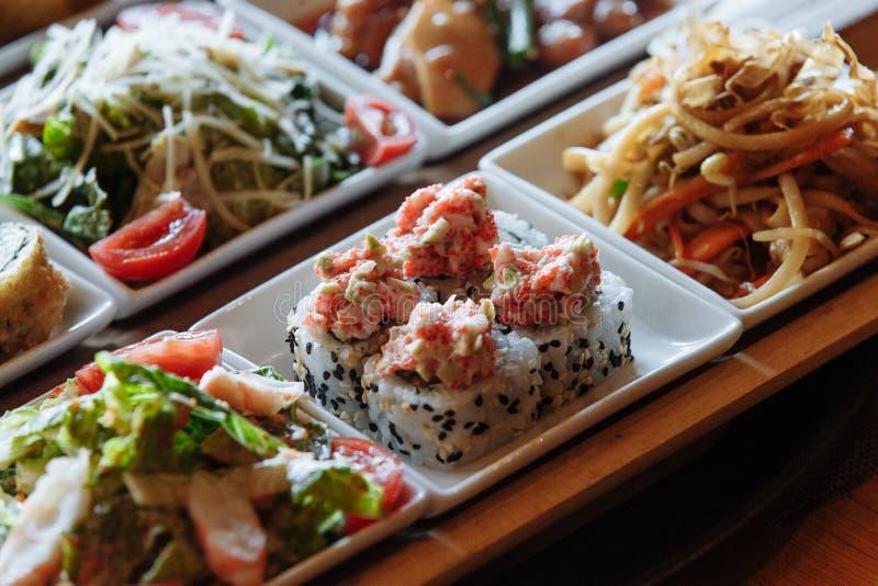 Сортированные японские блюда в белых квадратных плитах на деревянных стойках на предпосылке таблицы стоковые фото