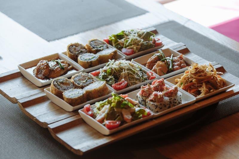 Сортированные японские блюда в белых квадратных плитах на деревянных стойках на предпосылке таблицы стоковые изображения