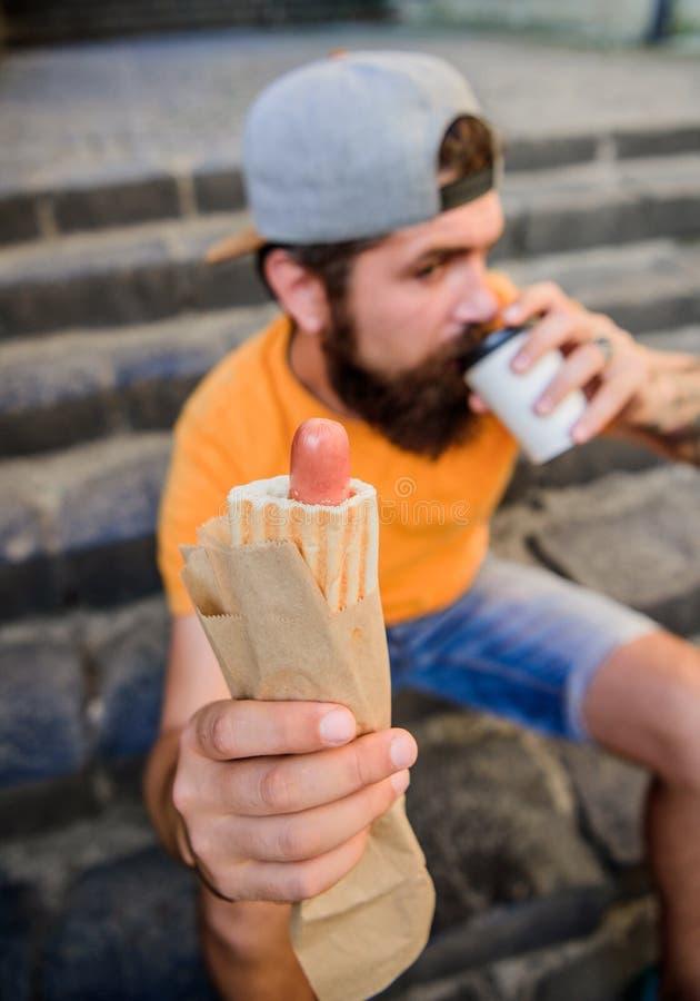 Сосиска бородатого укуса человека вкусные и бумажный стаканчик напитка Еда улицы настолько хорошая Городское питание образа жизни стоковая фотография rf