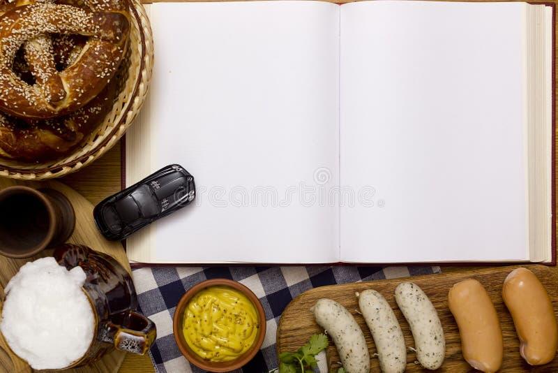 Сосиски, крендели, пиво и книга стоковое изображение