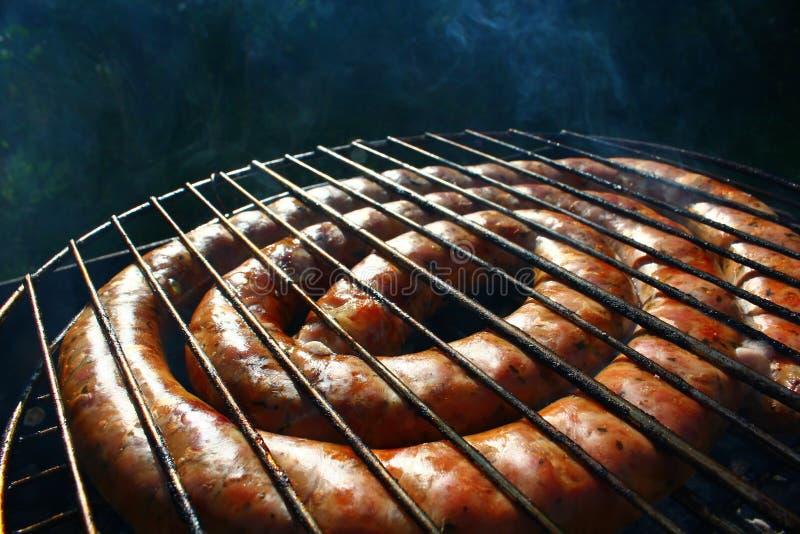 Сосиски BBQ сырцовые пламенистые на гриле стоковое фото rf