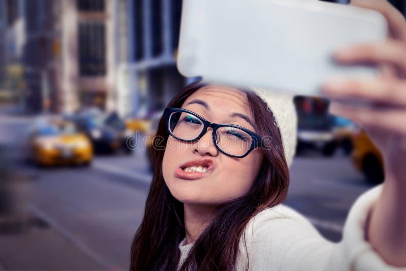 Составное изображение азиатской женщины делая стороны и принимая selfie стоковые изображения rf