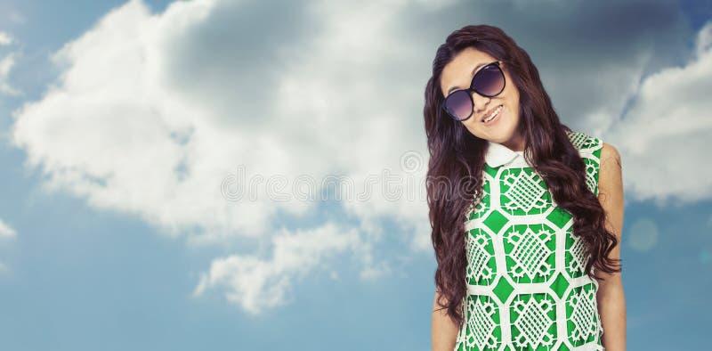 Составное изображение азиатской женщины при солнечные очки представляя для камеры стоковая фотография rf