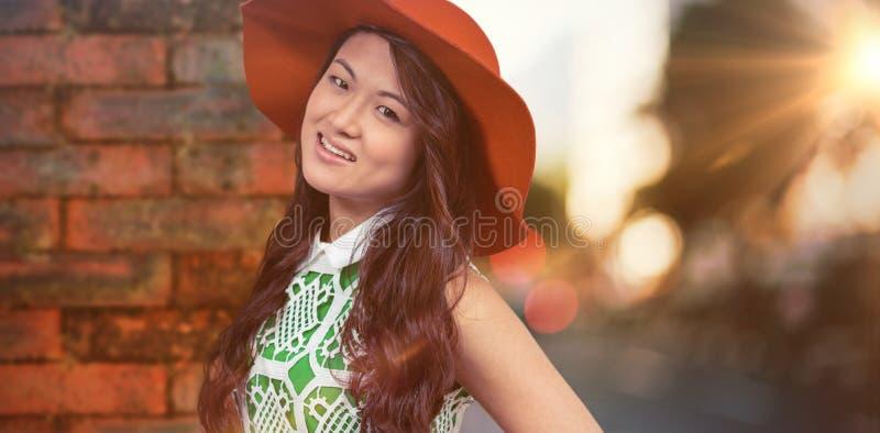 Составное изображение азиатской женщины при шляпа представляя для камеры стоковые изображения rf