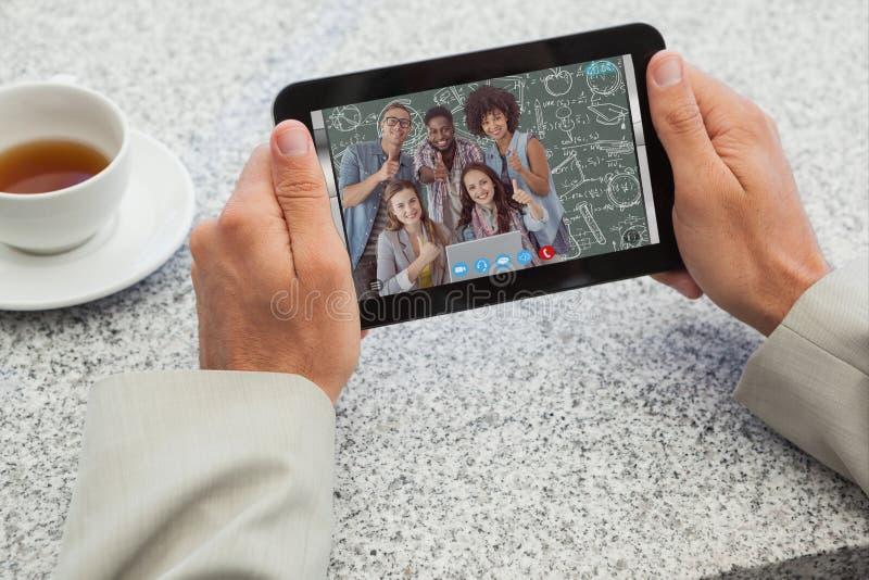 Составное изображение бизнесмена держа малую таблетку на таблице стоковое изображение rf