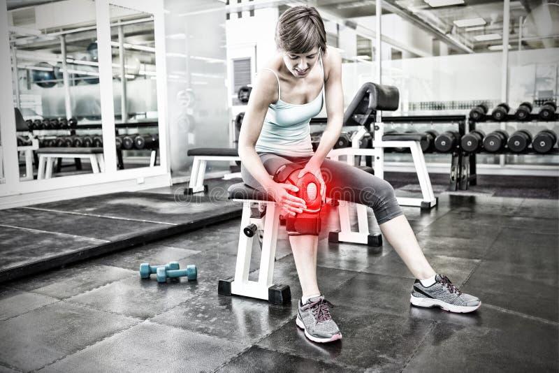 Составное изображение брюнет пригонки сидя на стенде держа раненое колено стоковые фотографии rf