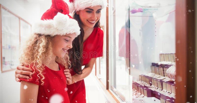 Составное изображение взгляда со стороны матери и дочери в одежде рождества смотря дисплей ювелирных изделий стоковая фотография