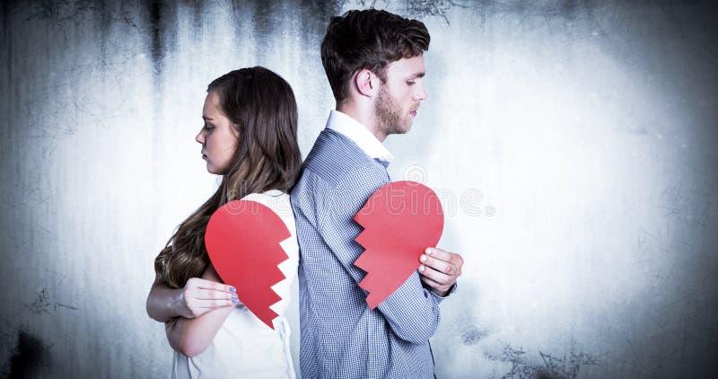 Составное изображение взгляда со стороны молодых пар держа разбитый сердце стоковая фотография rf
