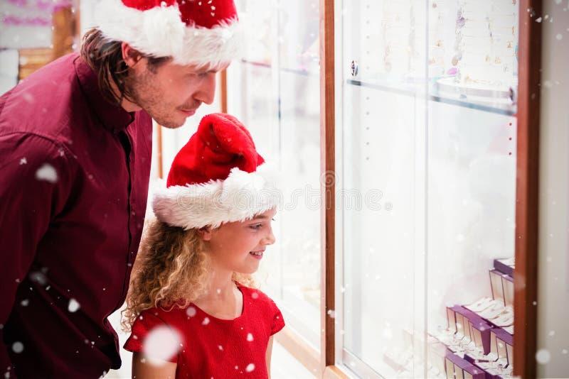 Составное изображение взгляда со стороны отца и дочери в одежде рождества смотря дисплей ювелирных изделий стоковая фотография rf