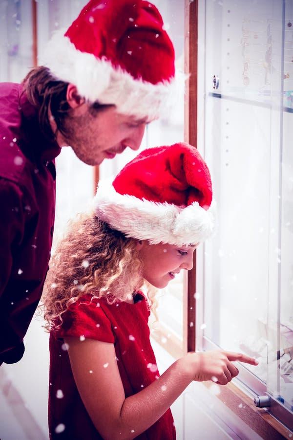 Составное изображение взгляда со стороны отца и дочери в одежде рождества смотря дисплей ювелирных изделий стоковое изображение rf