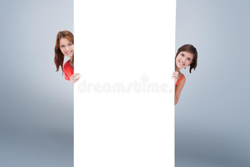 Составное изображение девочка-подростков пряча за пустым плакатом пока показывающ их голову от каждого sid стоковые фото