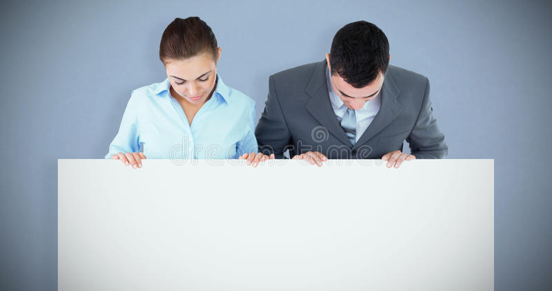 Составное изображение деловых партнеров смотря вниз на знаке они держат стоковое изображение rf